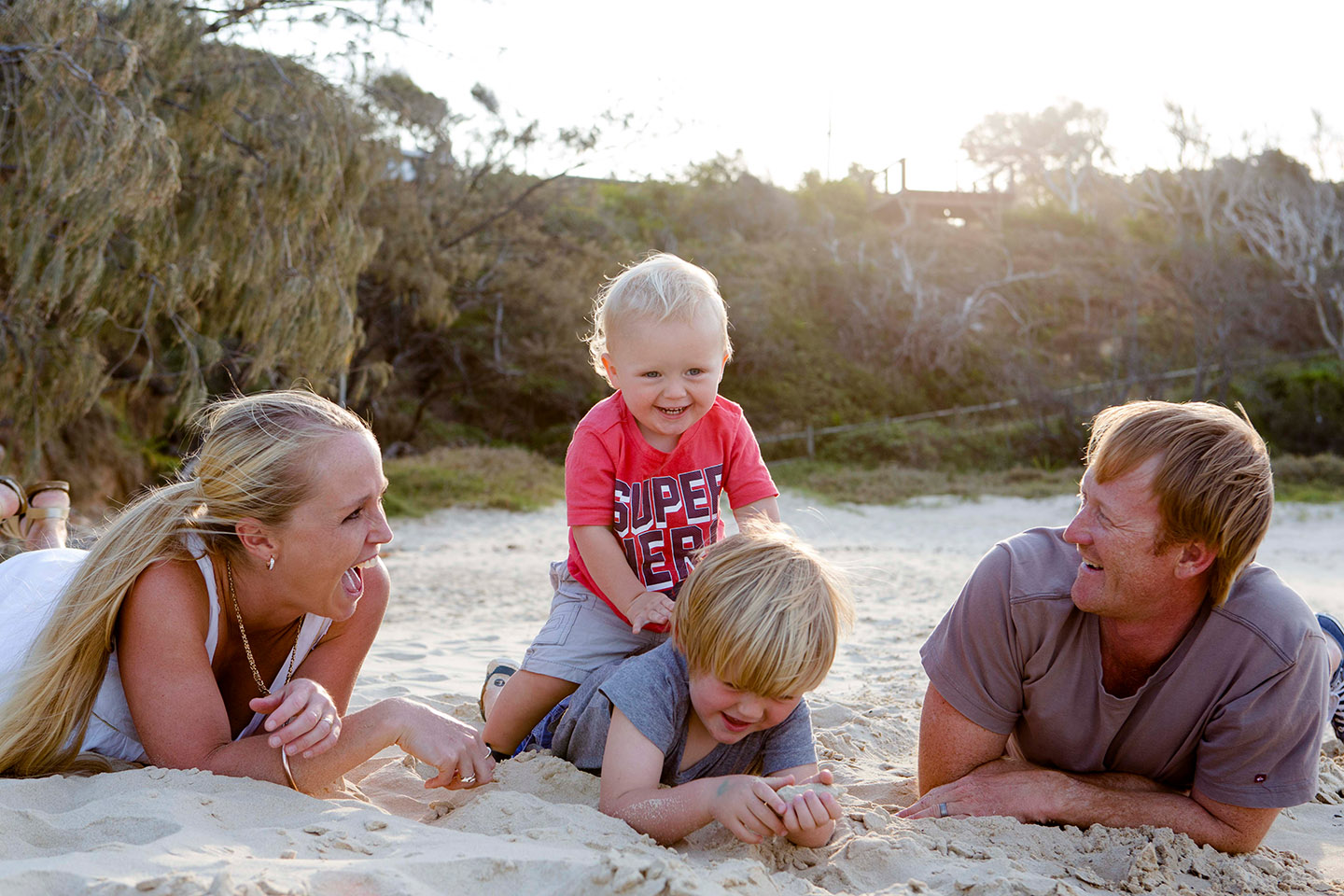 Family lying down on their tummies at the beach, the younger boy is seated on his brother back and parents laugh, Alice Payne photography