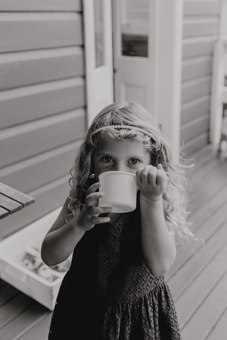 B&w image of a little girl drinking from a cup, children, family photography