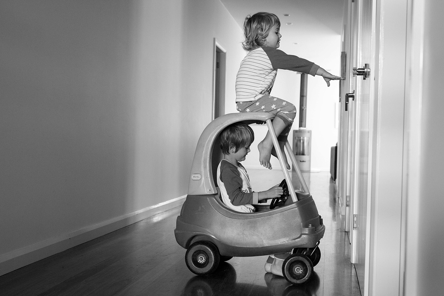 b&w image of two brothers, one isin a plastic car and the other is seatted on the top and trying to open the cupboard