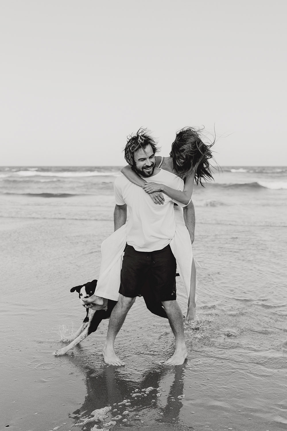 Black and white image of a couple having fun at the beach with their dog - Engagement photography - lovers -nambucca valley wedding photographer - Bellingen wedding photographer
