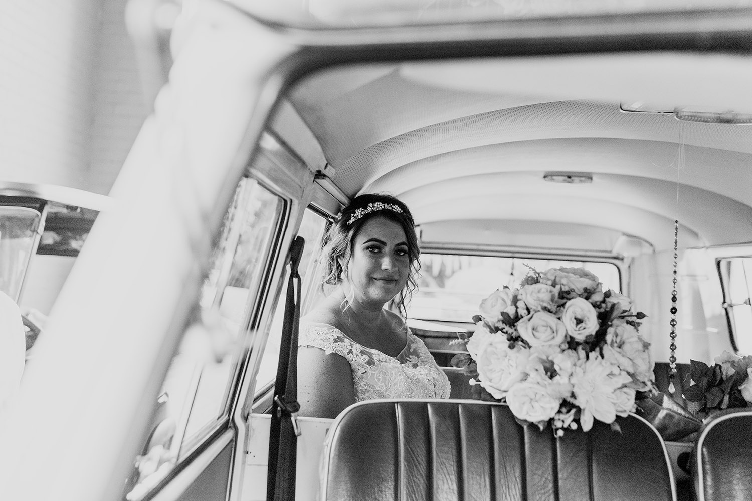 B&W image- Bride sitting in a VDub smiling holding flowers - Bellingen wedding photographer - Coffs coast wedding photographer - Nambucca Valley wedding photographer - Alice Payne photography