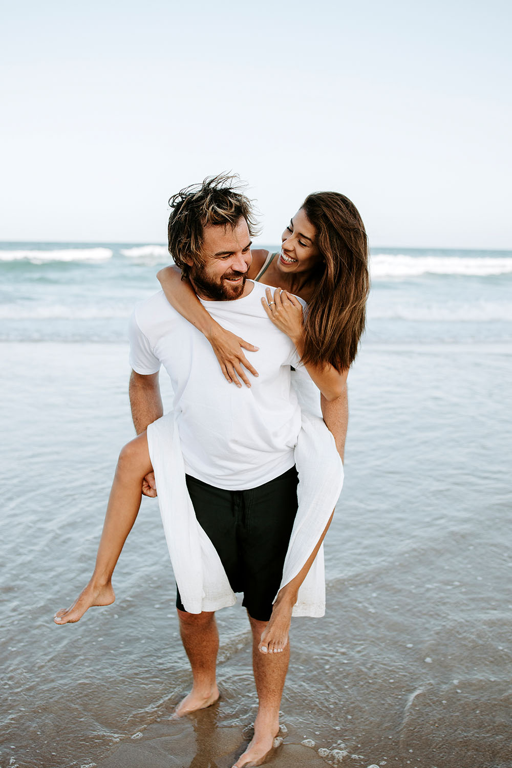 A boyfriend giving a piggy back to his girlfriend at the beach - Engagement photography - lovers- Nambucca valley  wedding photographer - Bellingen photographer