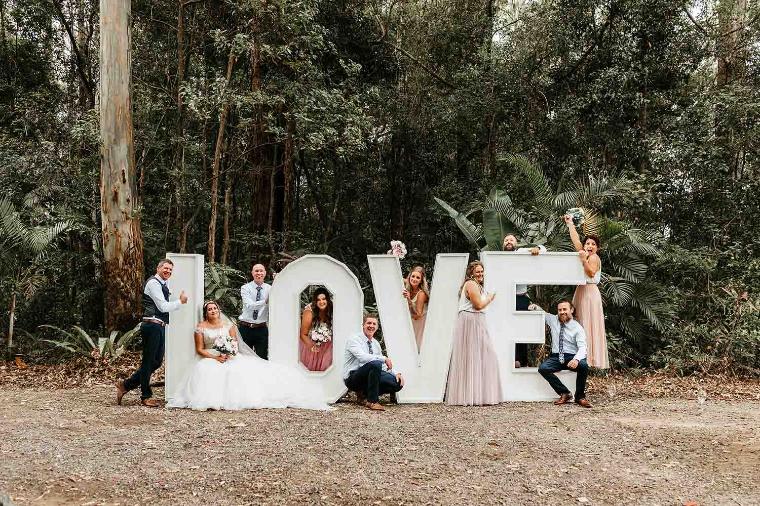 Bridal party interacting with big Love letters - Bonville Golf resot weddings - Bellingen wedding photographer -Coffs harbour wedding photographer -Nambucca wedding photographer