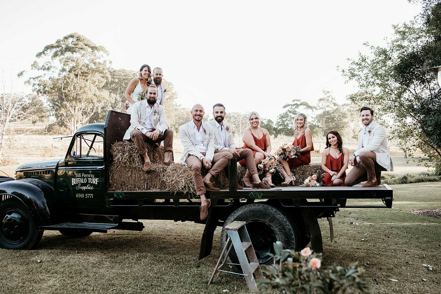 Bridal party sitting on hay on a old truck smiling - Eagle rest wedding -Nambucca valley wedding photographer - Bellingen wedding photographer - Coffs coast wedding photographer - elopment