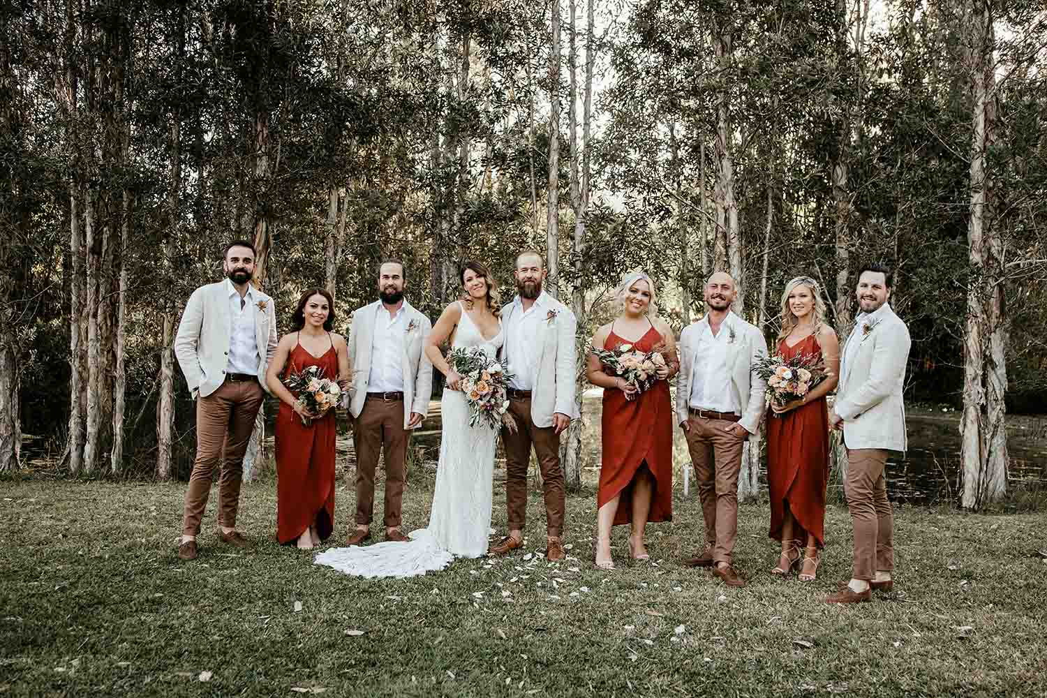 Bride and groom with their brodal party standing in a line smiling - wedding photographer - coffs coast wedding photographer - bellingen wedding photographer - nambucca valley wedding photographer - elopment
