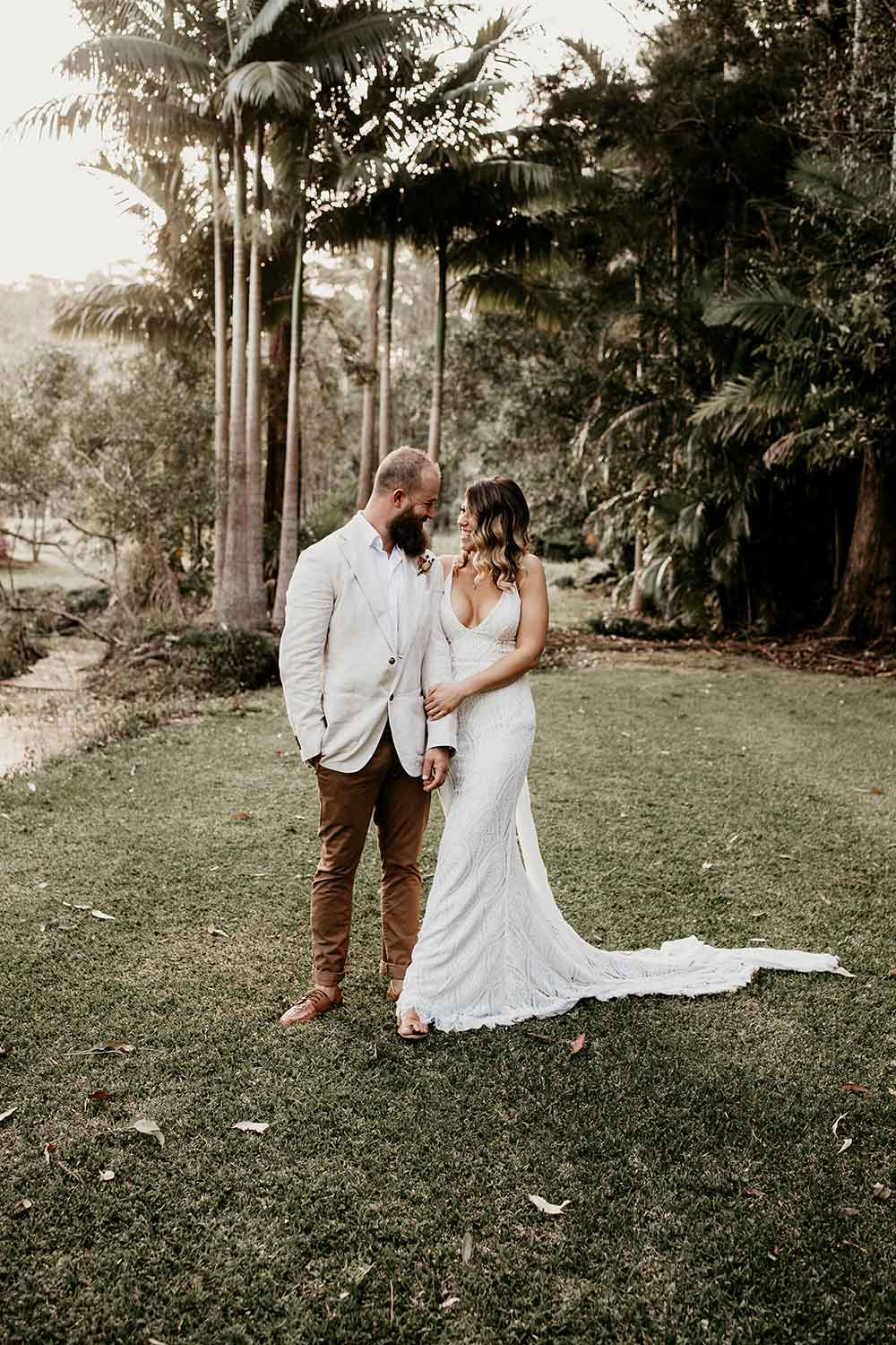 Bride and groom standing close holding each other looking at each other laughing - wedding photography - bellingen wedding photographer -nambucca valley wedding photographer - wedding dress- coffs coast wedding photographer