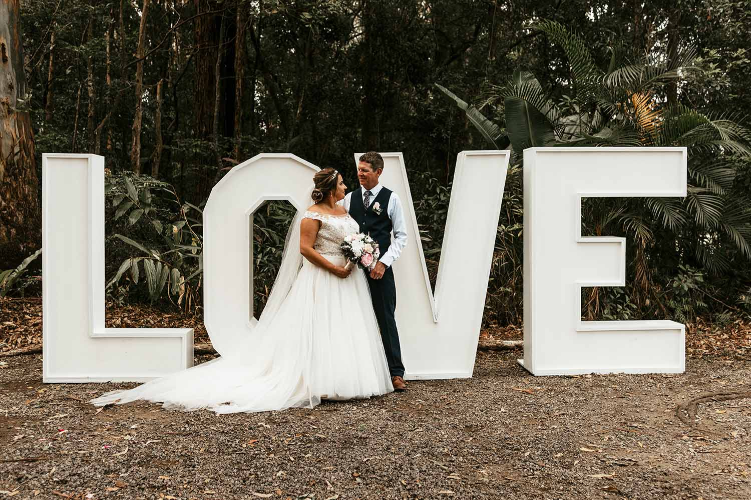Bride and groom looking at each other standing in front of a big love sign - Coffs harbour wedding photographer - Coffs coast wedding photographer - Bellingen photographer -  Nambucca Valley wedding photographer