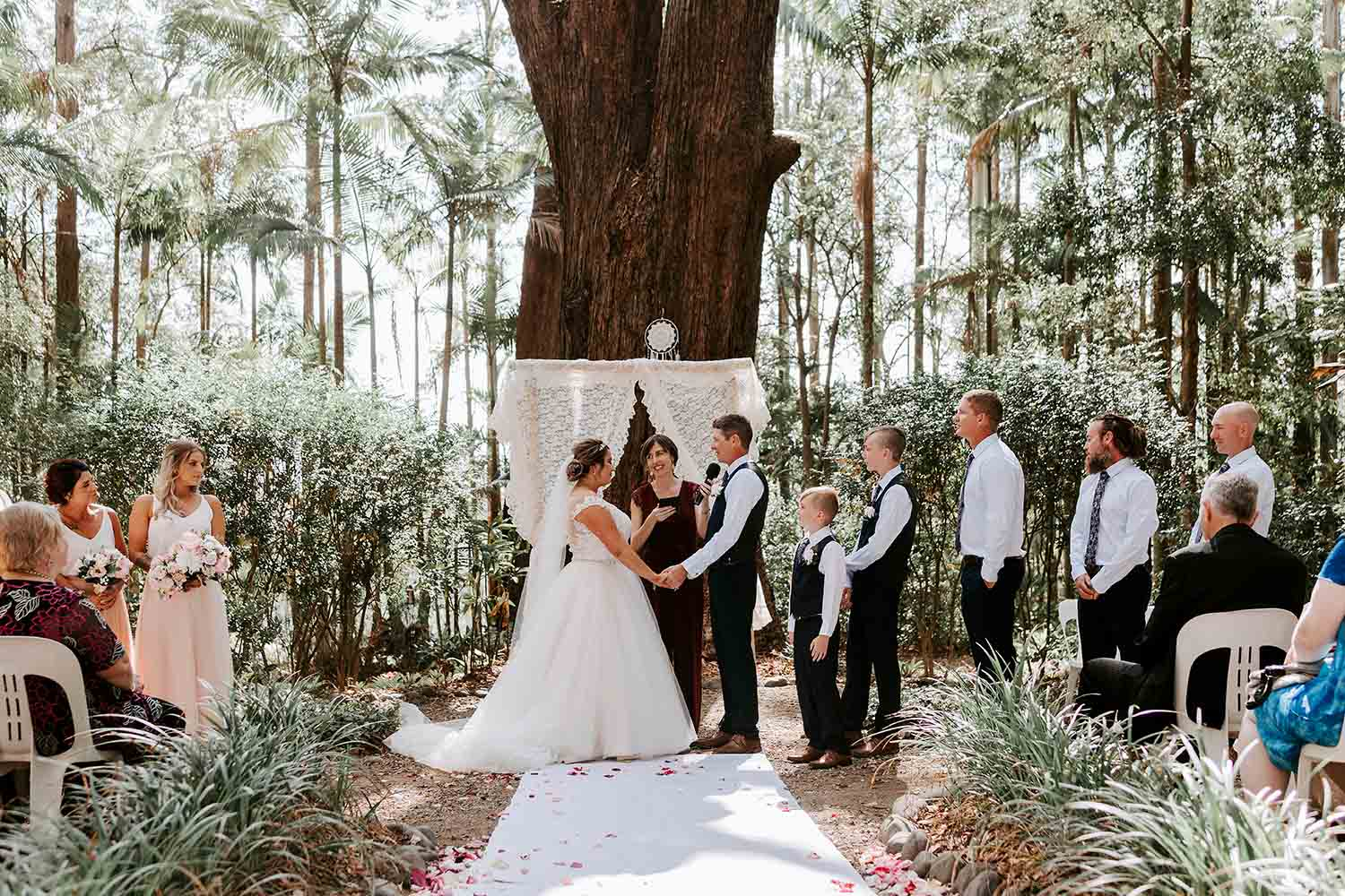 Bride and grrom holding hands at the ceremony - celebrant holds mics to Groom - Bellingen wedding photographer - Nambucca Heads Wedding photographer - Coffs Harbour wedding photographer