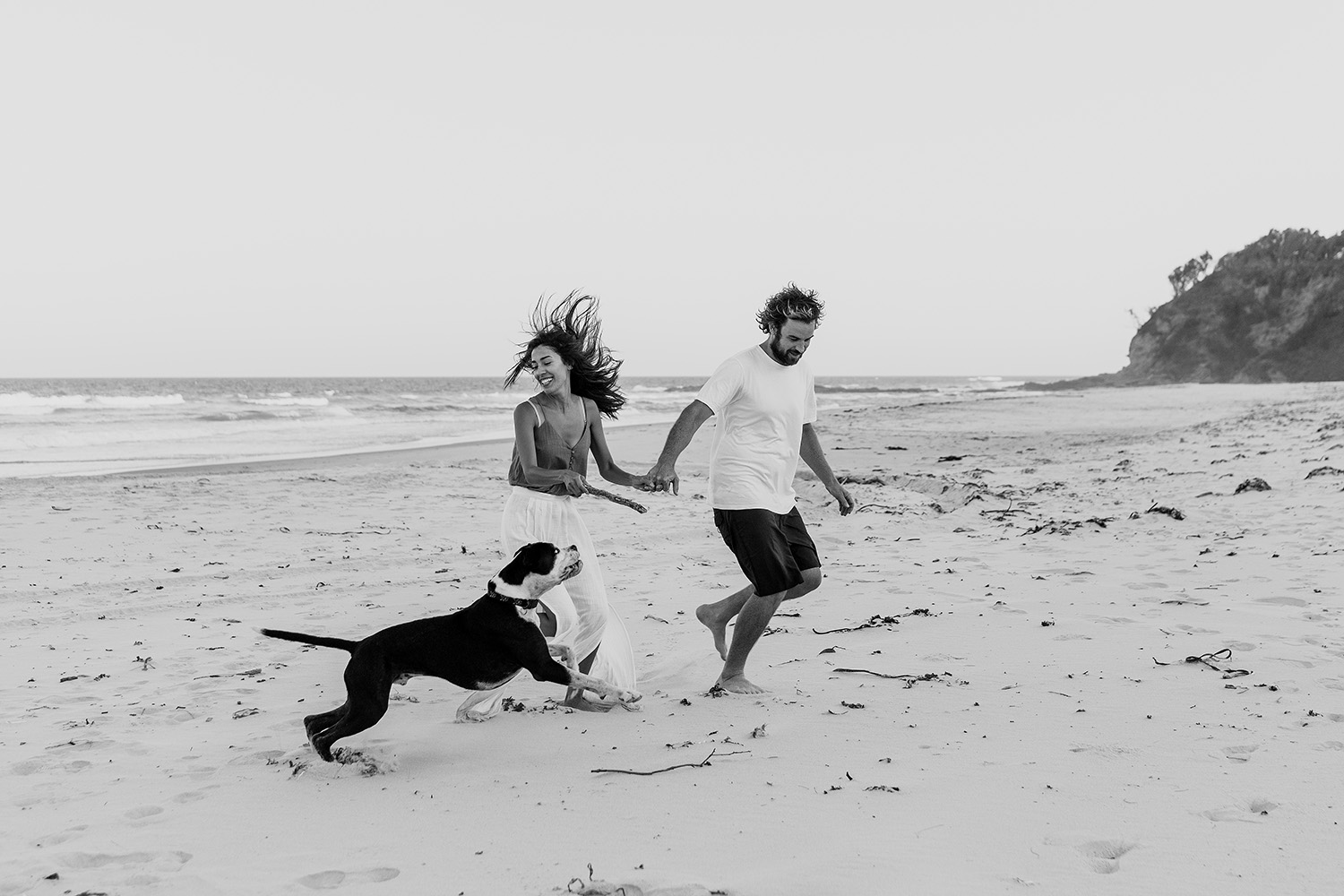 Laughing Couple playing with their dog at the beach - mid north coast Wedding photographer - Bellingen wedding photographer -engagement photography