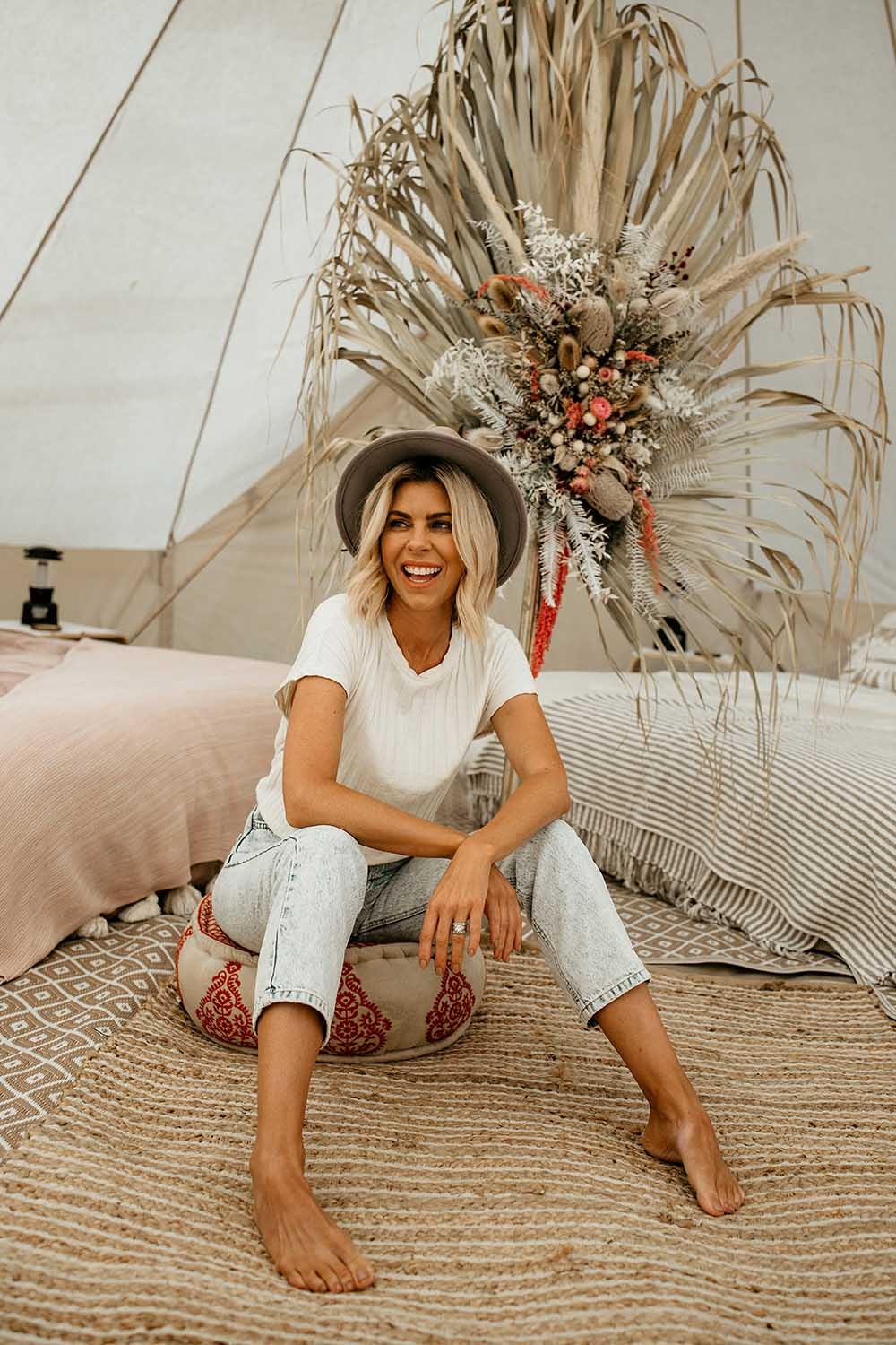 Fashion model laughing sitting in a bohemian setting in a bell tent - glamping - lifestyle photographer - business branding photography - Nambucca valley photographer - Bellingen photographer - Coffs coast photographer