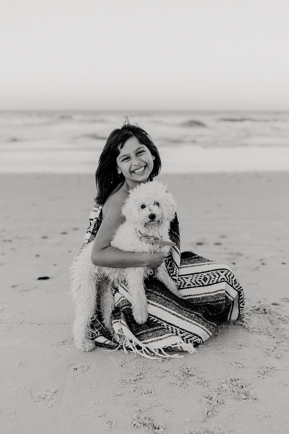 A girl is holding her little dog at the beach - family photography - lifestyle photography - Nambucca valley photographer - Bellingen photographer - coffs coast photographer