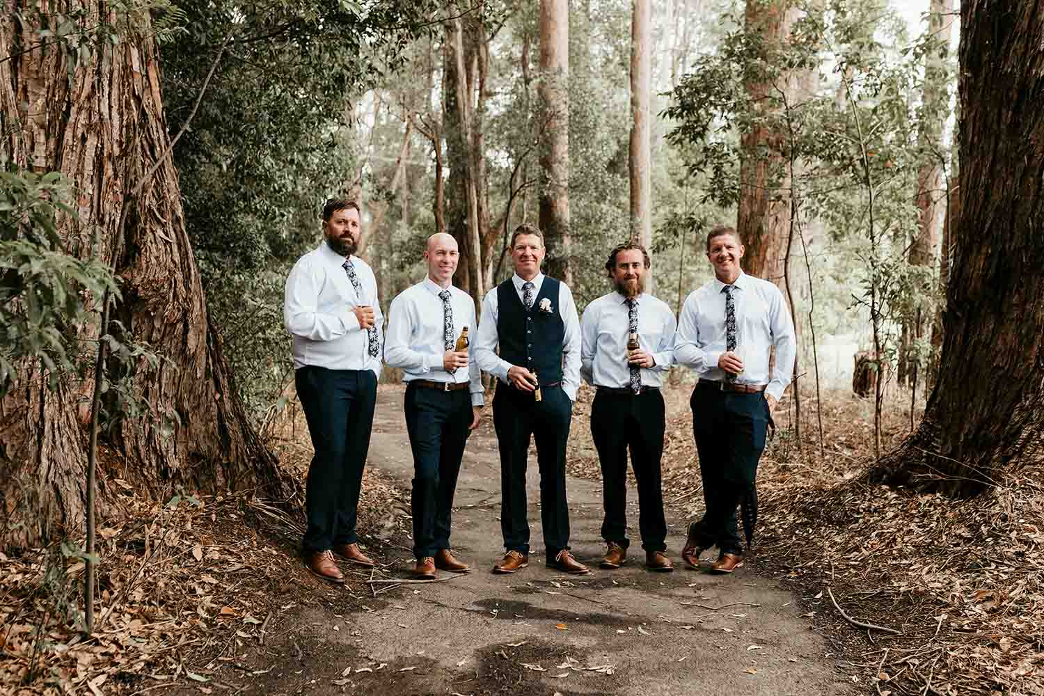 Groomsmen standing in a line smiling and holding a beer - Bellingen wedding photographer - Coffs harbour wedding photographer - Nambucca heads wedding photographer