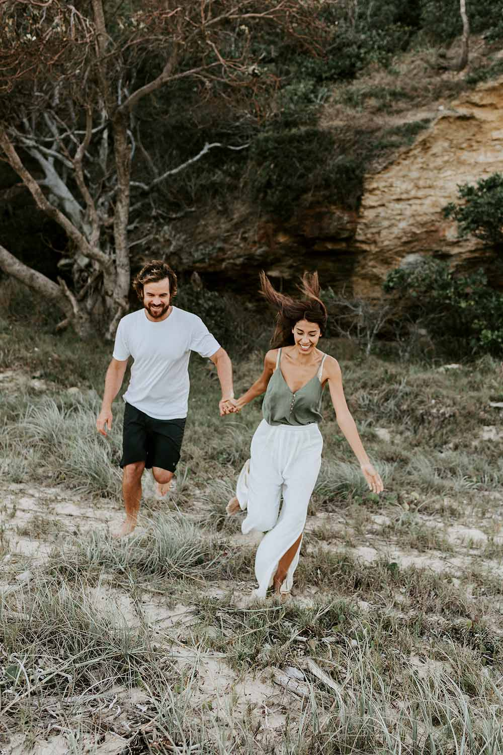 Laughing couple holding hands running at the beach - engagement - nambucca valley wedding photographer -Coffs coast photographer