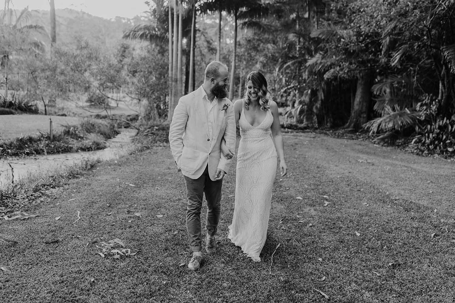 Bride and groom walking holding hands looking at each other laughing - wedding photographer - mid north coast wedding photographer - Nambucca valley photographer - elopment