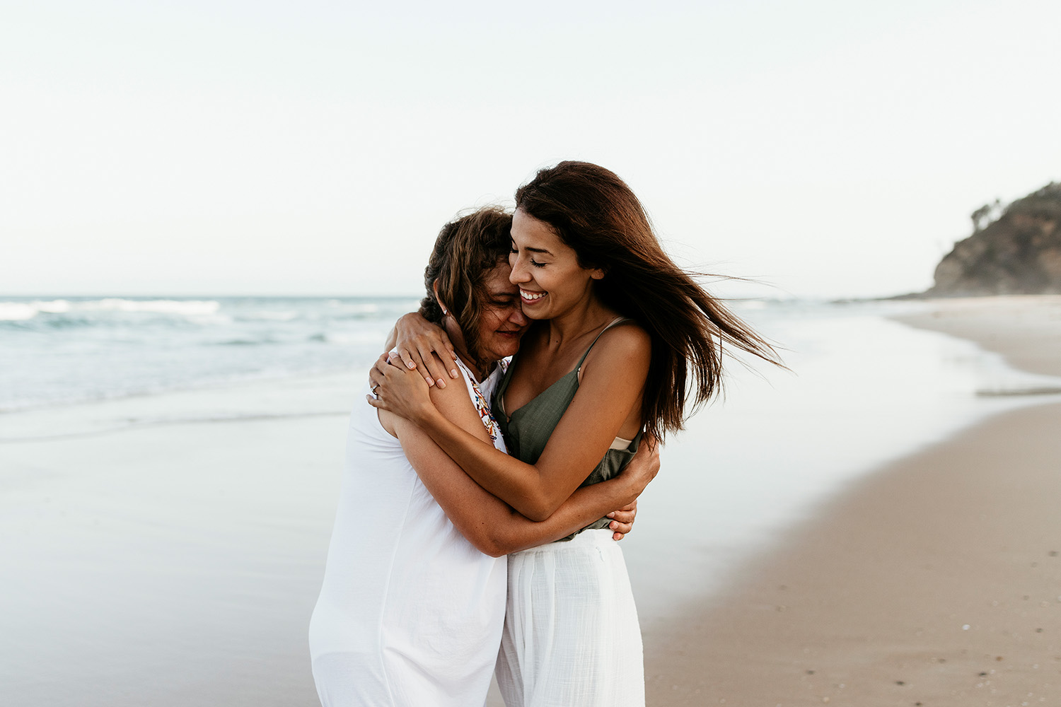 Mother and daughter cuddling smiling at the beach - Nambucca valley family photographer - Bellingen family photography