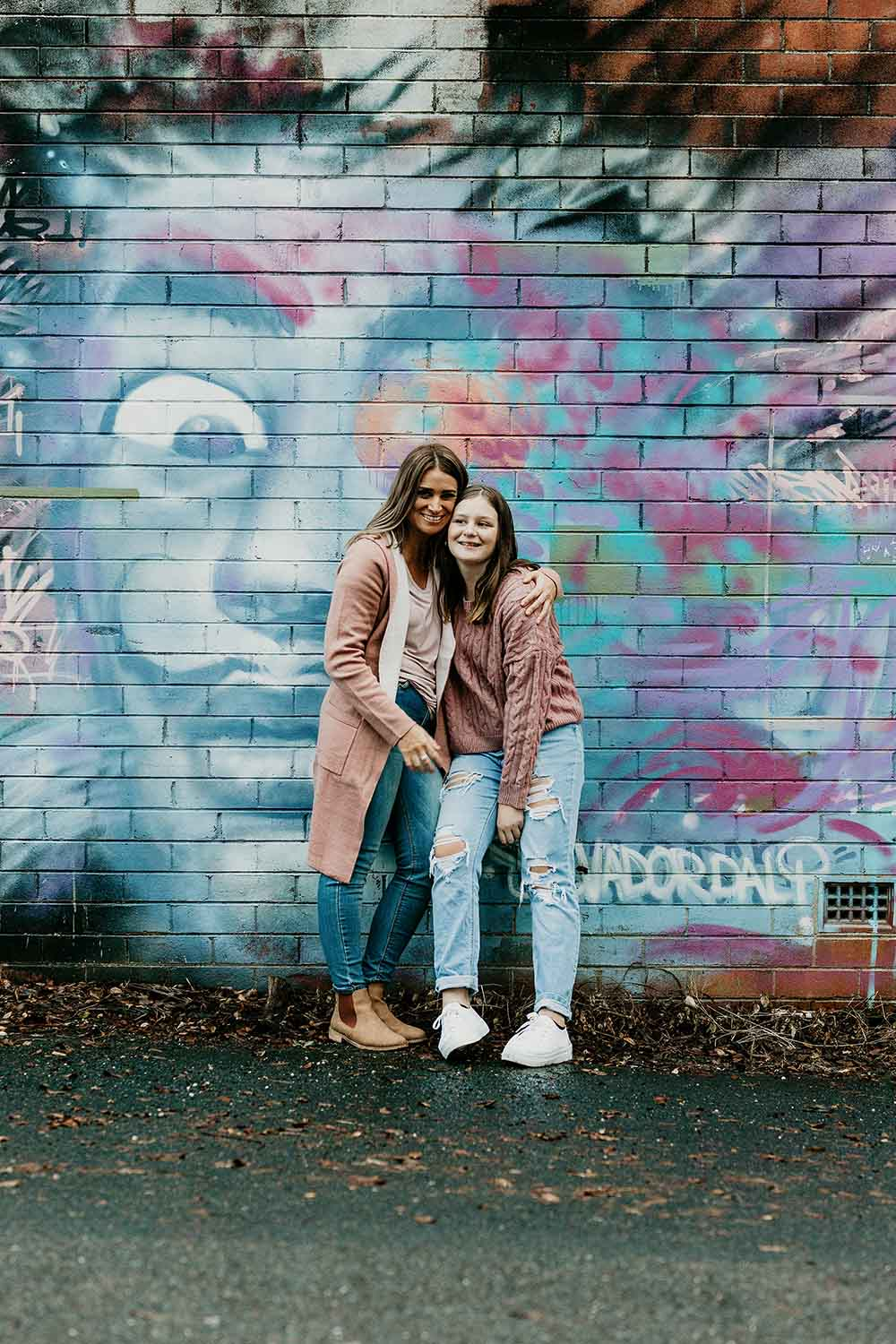 Mother and daughter holding each other and standing in front  of graffiti art - family photographer -motherhood photography - bellingen family photographer -nambucca valley familly photographer - Coffs harbour family photographer