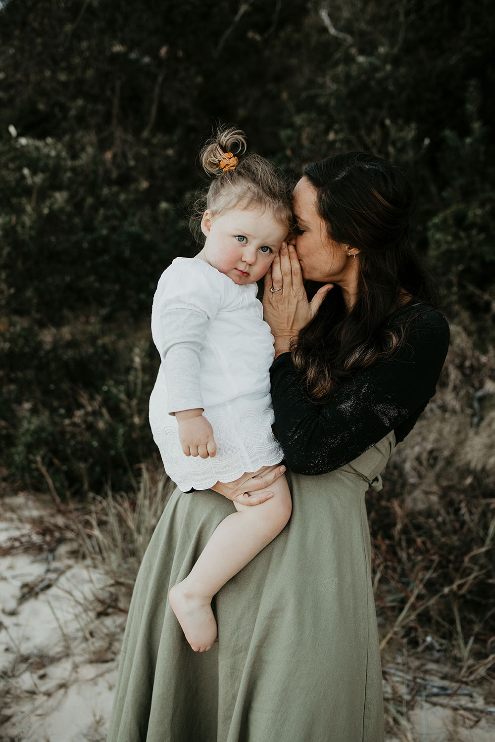 Mother holding her daughter and whispering a secret in her baby girl's ear - Motherhood photography -family photography - Nambucca valley photographer - bellingen photographer -coffs coast photographer