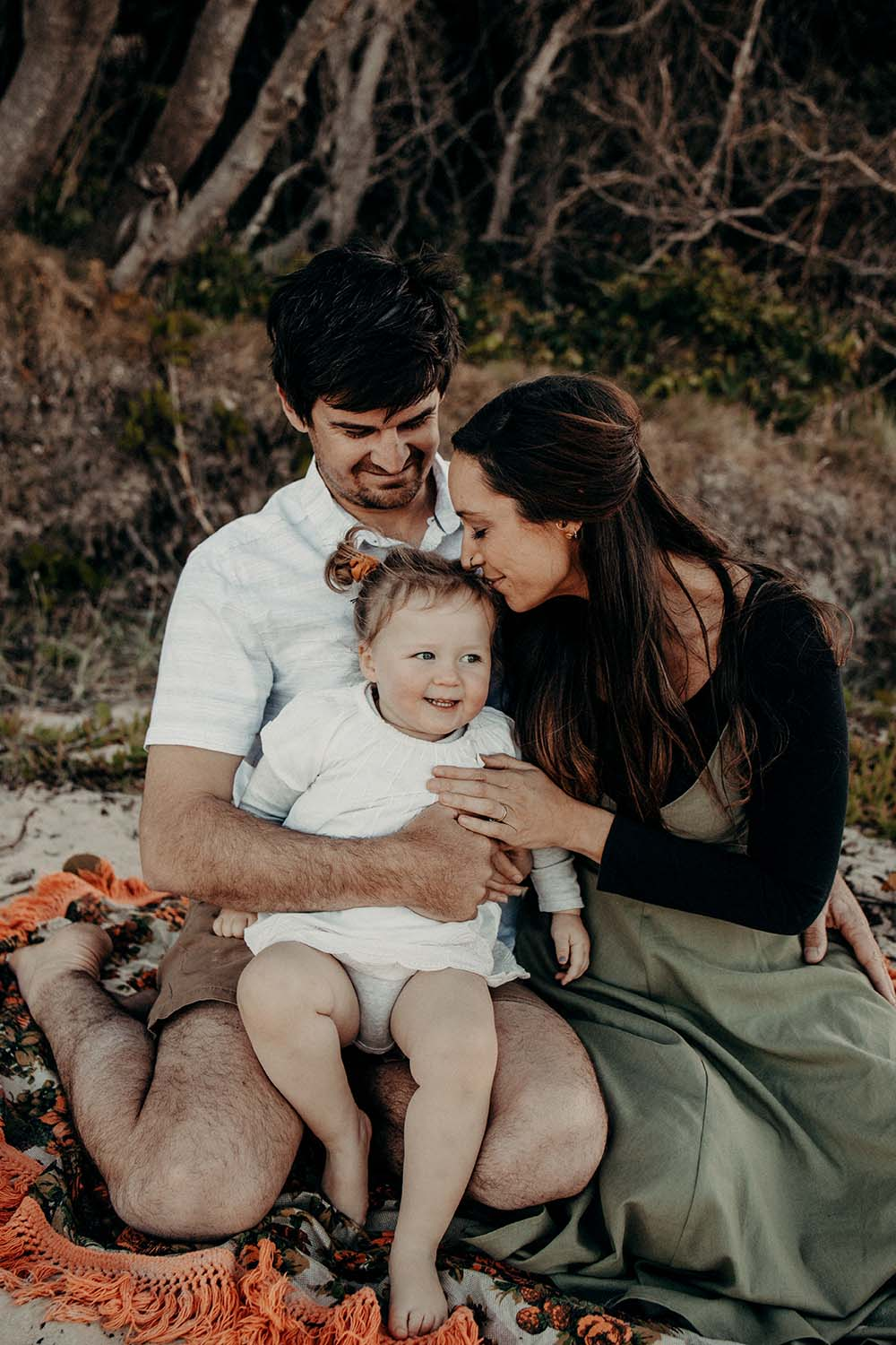 Parents holding thier baby girl and kissing her on the head - family photographer - bellingen photographer -Coffs coast photographer - Nambucca heads family photographer -Nambucca valley photographer