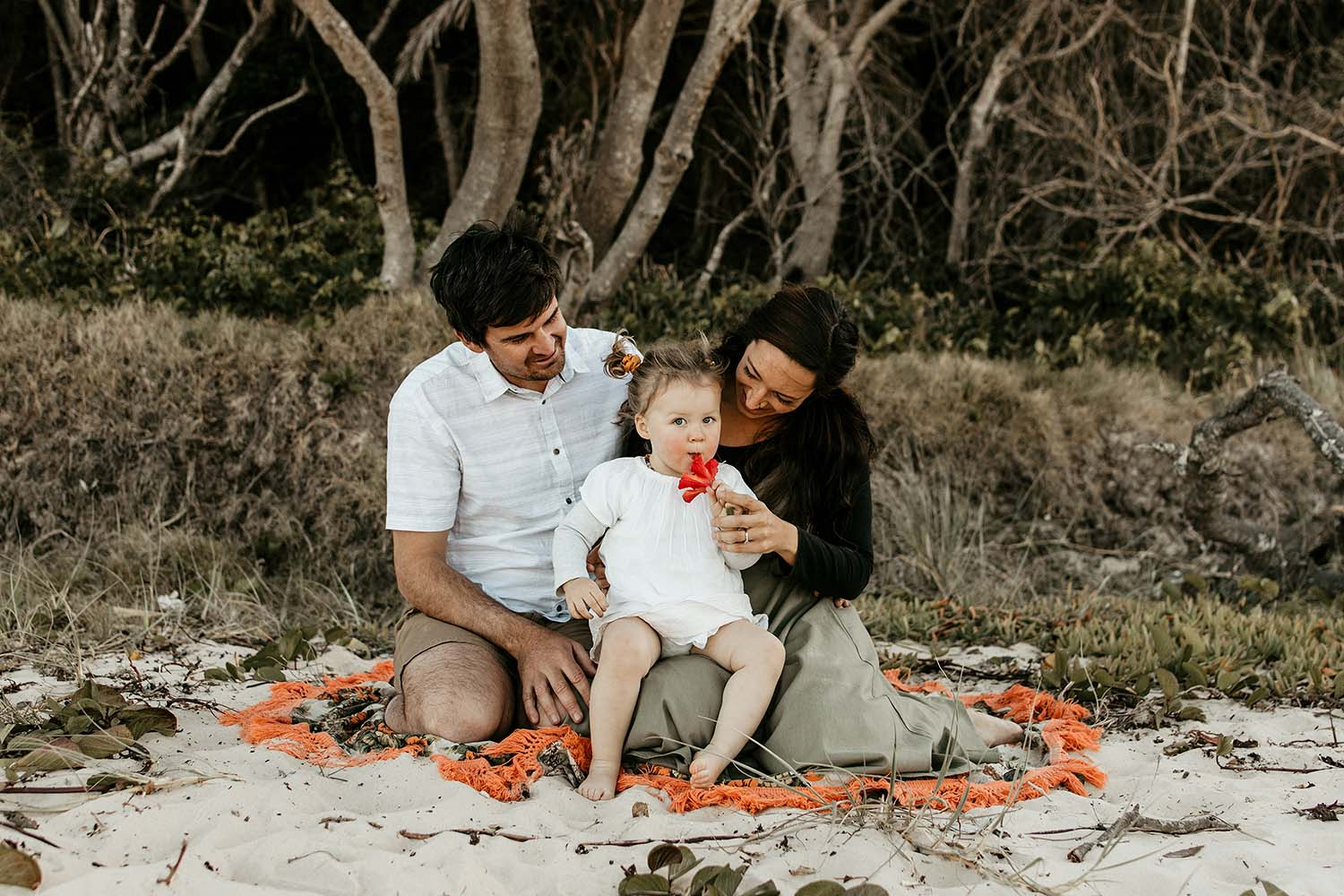 Parents with their baby girl sitting on the sand all cuddling - family photographer -Bellingen photographer - Nambucca heads photographer - Coffs coast photographer
