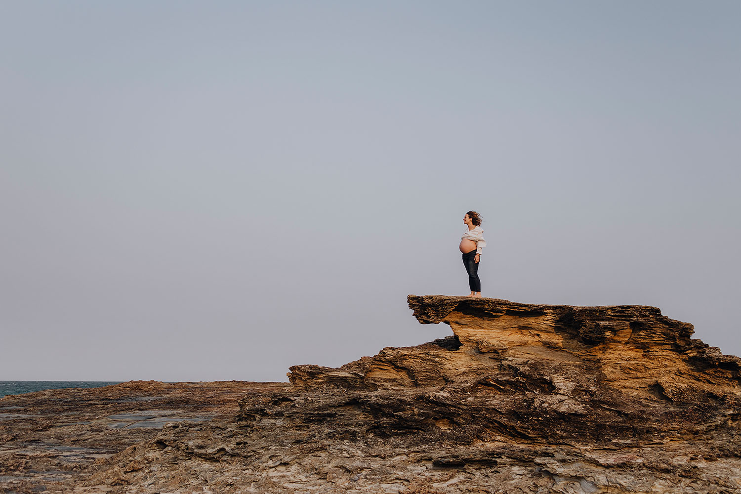 Pregnant woman standing on a rock looking at the ocean - maternity photography -newborn photographer - coffs coast photographer - Nambucca valley photographer - bellingen photographer