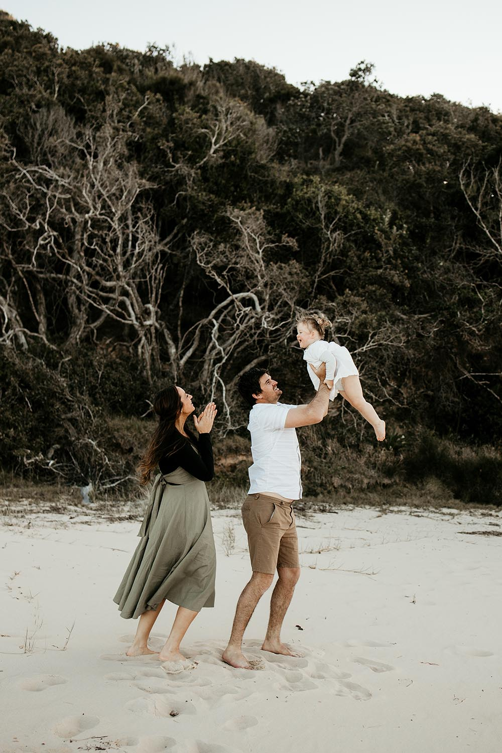 Father throwing his baby girl in the air mother laughing - family photographer -nambucca valley photographer - Coffs coast photographer - bellingen photographer -