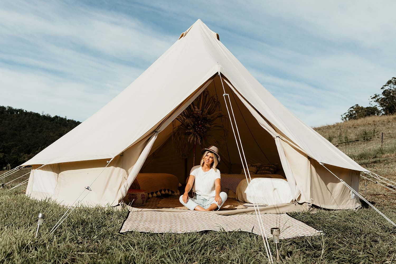 Fashion model sitting in front of a bell tent smiling - lifestyle photography - business branding photography - Nambucca valley photographer - Bellingen photographer - Coffs coast photographer